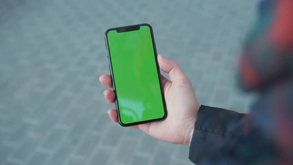 NEW YORK - April 5, 2018: Close up hands woman holding phone with vertical green screen on busy street background pavement scrolling pages swiping surfing internet technology chroma key message