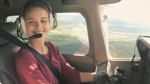 Gorgeous model piloting a small private plane looking around and smiling