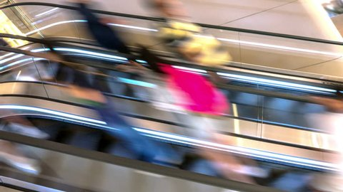 Timelapse of people move fast on escalator. Blurred defocused commuters abstract view