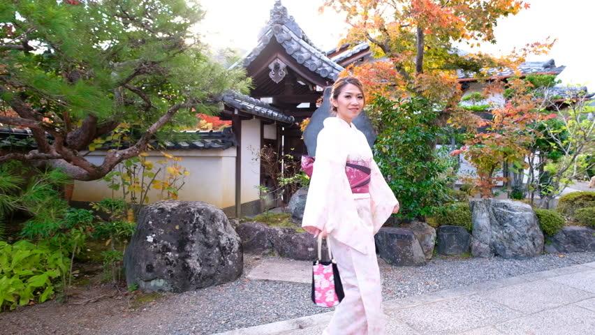 4K Crane shot : A Asian woman wearing Kimono Dress walking at japanese garden inside Tenryuji Temple with Autumn leaf Color. - welcomes you to Japan | Shutterstock HD Video #1025940476