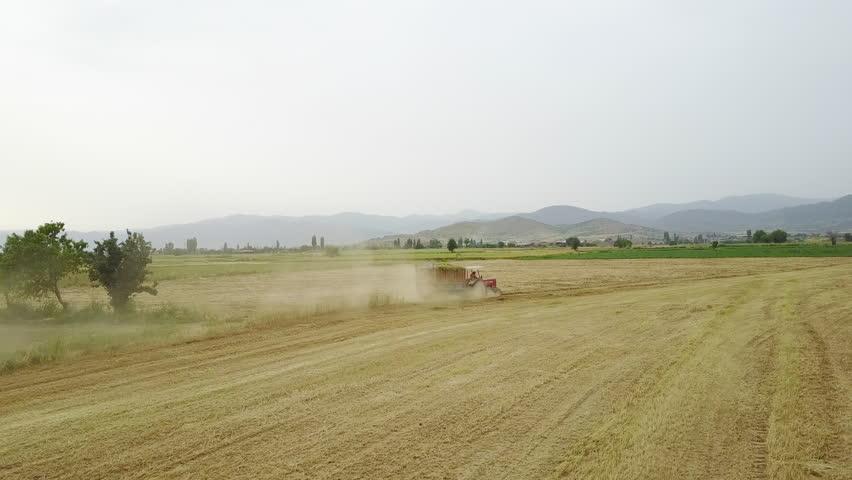 Drone camera following a tractor in a large field | Shutterstock HD Video #1025942996