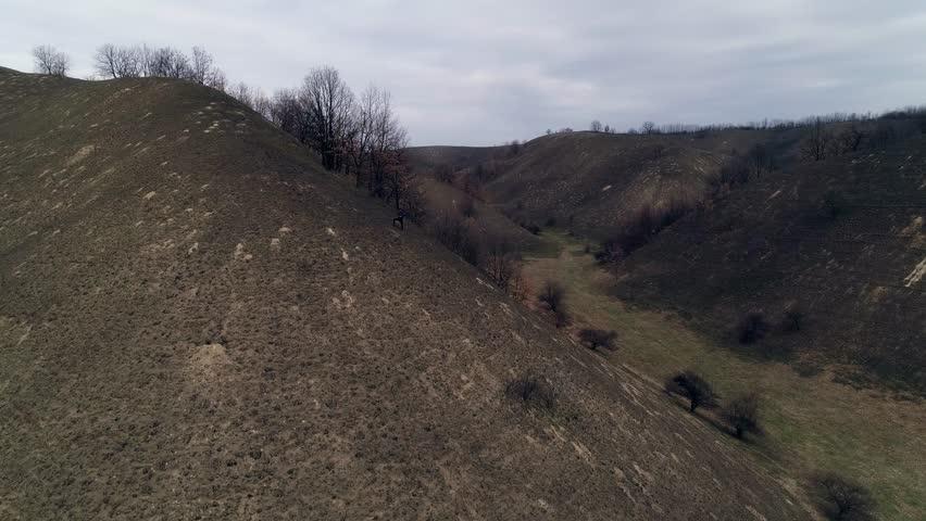 Flight through hilly landscape. Burnt grass. Camera ascending, reveals landscape | Shutterstock HD Video #1025946326