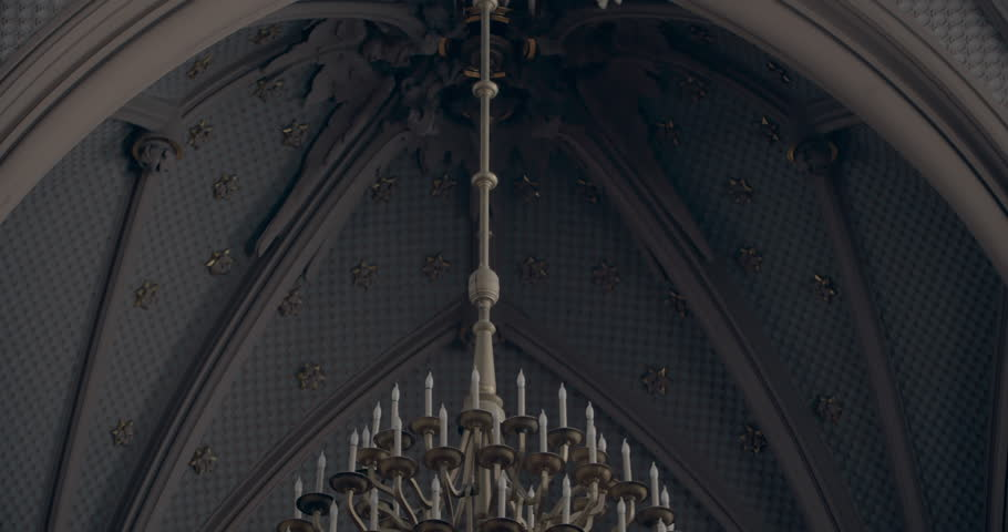 Panoramic view of gothic church interior with two people inside. Cathedral with organ music. High cells with historical light. Jesus Christ portrait on the wall. Vintage gothic style Chandelier.  Cold | Shutterstock HD Video #1025948246