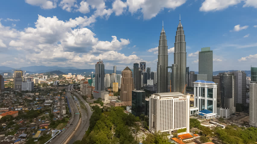 Aerial view of a city skyline with busy streets and expressway of  Malaysia on a blue skies.  Zoom out motion timelapse | Shutterstock HD Video #1025955086