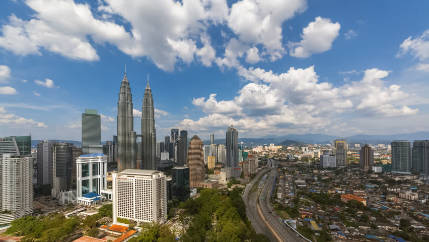 Aerial view of a city skyline with busy streets and expressway of  Malaysia on a blue skies.  | Shutterstock HD Video #1025974916