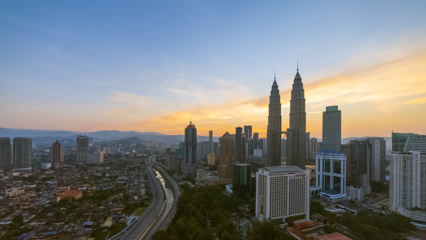 Aerial time lapse view of a city skyline with busy streets and expressway of  Malaysia at sunrise from twilight to day.   | Shutterstock HD Video #1025974976