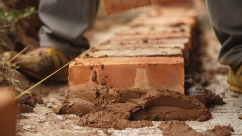 Close up of African builder laying brick and scooping brown cement mixture with trowel