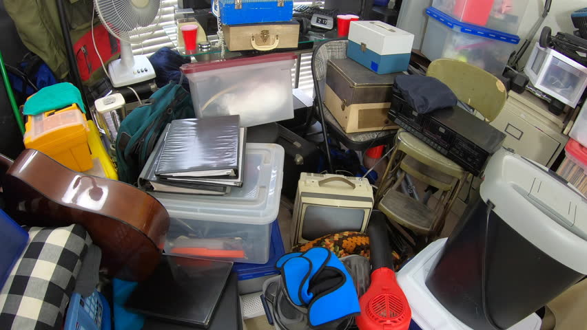 Cluttered object filled room.  Slow dolly out over piles of household items, vintage electronics, business equipment and miscellaneous junk. | Shutterstock HD Video #1025996816