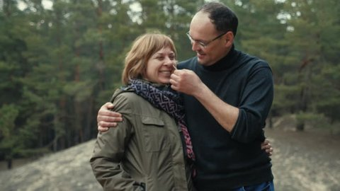 Funny adult man tickles his happy wife with a spikelet in the forest