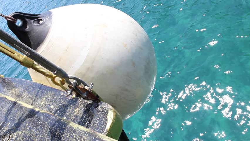 White buoy hanging on a sailing ship