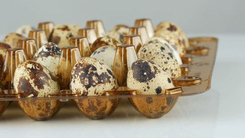 Fresh meat of quail in a plastic brown tray next to the quail eggs on a white background rotate