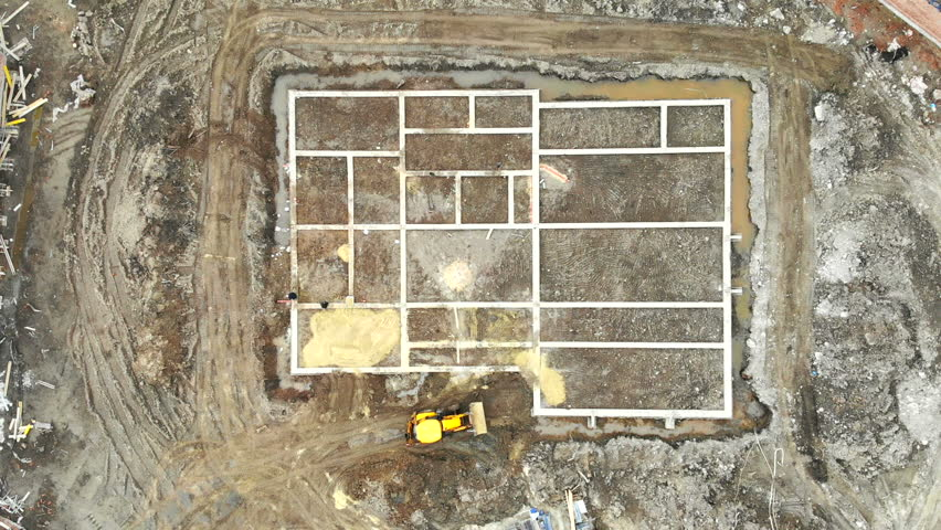 Aerial view on top building foundation. The excavator brings sand for the foundation of the house | Shutterstock HD Video #1026018296