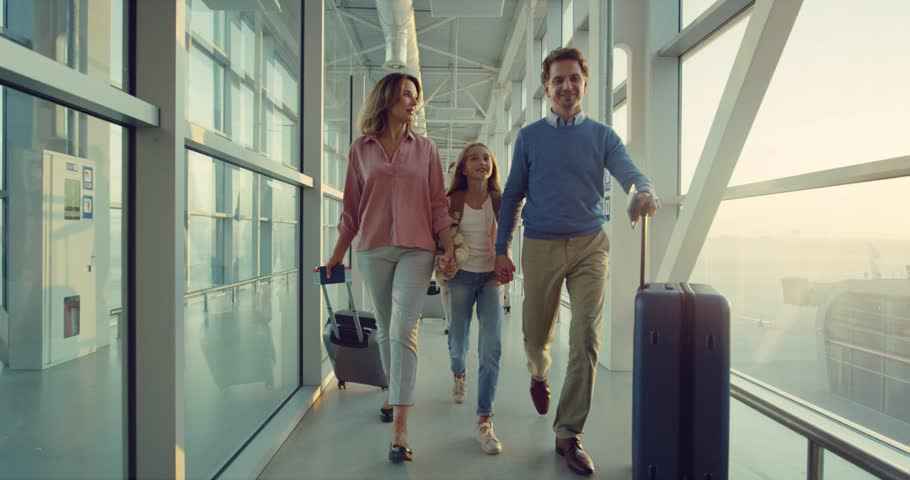 Caucasian cheerful parents and their teen cute daughter walking the passage at the airport with suitcases happily. | Shutterstock HD Video #1026022526