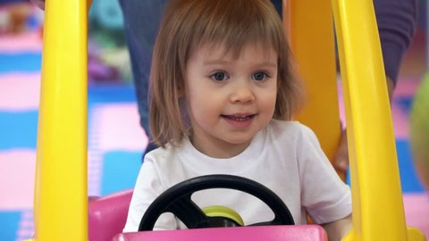 A little pretty girl is sitting in a beautiful, bright children's car behind the wheel, in a children's play center. Turns the steering wheel, smiles and laughs