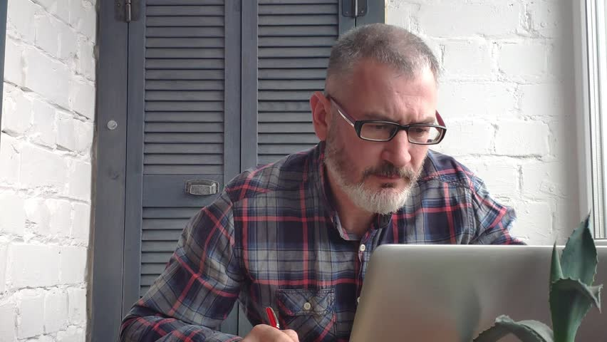 Gray-haired bearded male accountant working at home behind a laptop, making a report against the backdrop of a minimalist interior, verifies data with the monitor, checks the data on the phone. | Shutterstock HD Video #1026095006