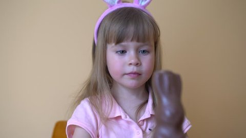 Little cute girl child eats a chocolate hare. The girl has bunny ears on her head. Beautiful girl holding Easter chocolate bunny in her hands.