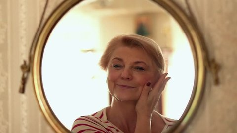 Senior, happy woman checking her look in front of the mirror, slow motion