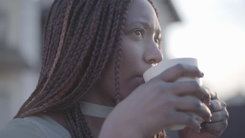 Close up portrait of confident african american young black smiling woman with hot cup of coffee on the street. Slow motion   Shutterstock HD Video #1026158876
