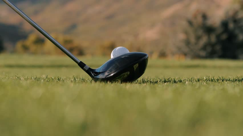 Man drives golf ball on tee close up with grass flying. Close up view of a golf ball on tee being hit by a golf club. The video shows grass flying off the ground after the hit. | Shutterstock HD Video #1026193736
