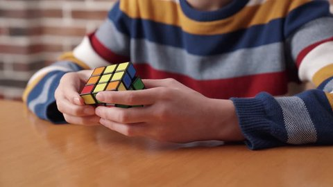 Moscow, Russia – March 24, 2019: A boy assembling the Rubik's cube. Rubik's Cube is a 3D combination puzzle invented in 1974 by Hungarian sculptor and professor of architecture Erno Rubik