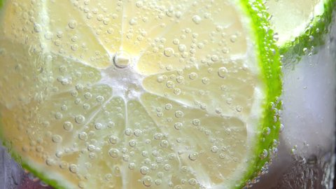 Macro close-up refreshing cold cocktail with lime. soda water covered with bubbles. Slice of lemon with bubbles. 4K UHD video