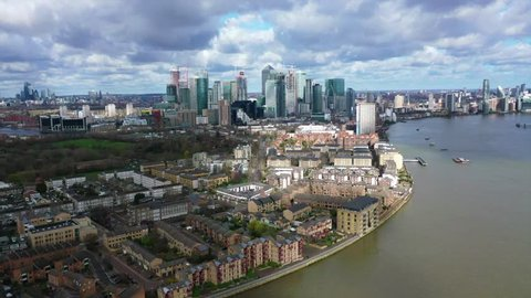 Docklands, London / United Kingdom - March 18 2019: Aerial bird's eye panoramic video taken by drone of iconic Canary Wharf skyscraper complex and business district with beautiful clouds, Isle of dogs