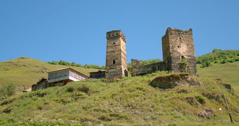 Zoom out shot of Stone medieval Svaneti tower houses of Davberi village in the Caucasus mountains, Upper Svaneti, Samegrelo-Zemo Svaneti, Mestia, Georgia. A UNESCO World Heritage Site.