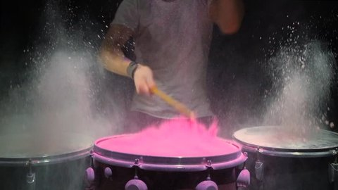Red holi powder bounces off drum in shockwave pattern, slow motion. black background.