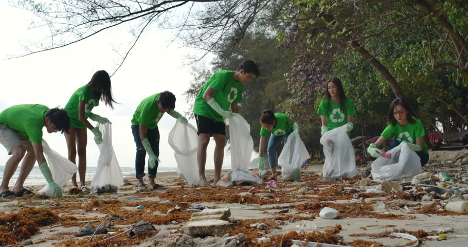 Group of young asian people volunteers in green t-shirts cleaning up the beach with plastic bags full of garbage. Safe ecology concept. 4k resolution. | Shutterstock HD Video #1026301046