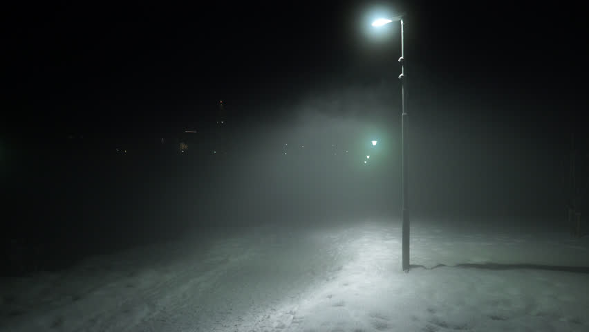 Man walking disappearing into fog under street lights Reykjavik Iceland park winter night