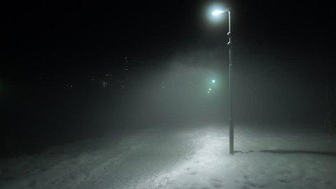 Man walking disappearing into fog under street lights Reykjavik Iceland park winter night