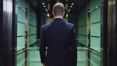young well dressed businessman comes into modern elevator with large mirror and door closes slow motion backside view
