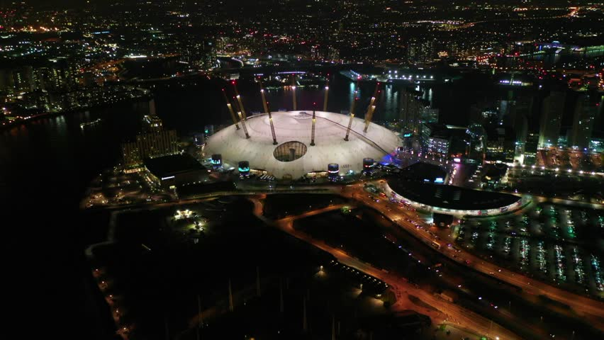 Greenwich Peninsula, London / United Kingdom - March 18 2019: Aerial drone bird's eye night view video of iconic concert Hall of O2 Arena
