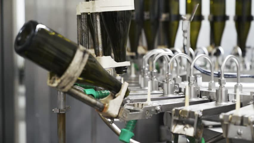 Slow-motion, glass bottles on the automatic conveyor line at the champagne or wine factory. Plant for bottling alcoholic beverages   Shutterstock HD Video #1026448316