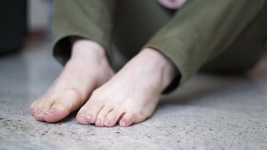 Close-up of woman's hands putting on black socks  on her feet. Woman wearing colored socks on the marble ground. front view #1026525326