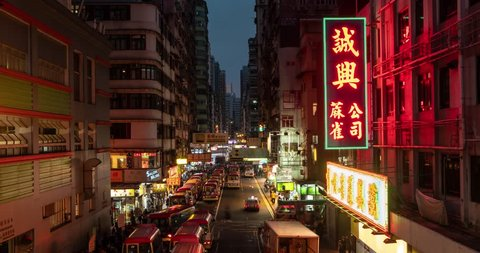Time lapse of busy street with traffic and pedestrians of Mong Kok at night in Hong Kong. 4K.