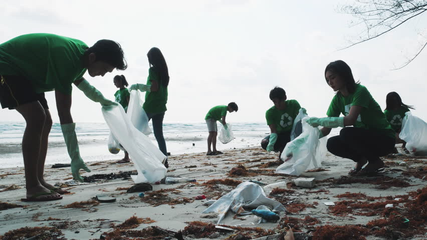 Asian group volunteer member cleaning summer beach and keeping garbage together in cleaning day. Concept of waste environment, recycle, ecology, pollution and volunteer. 4k resolution.