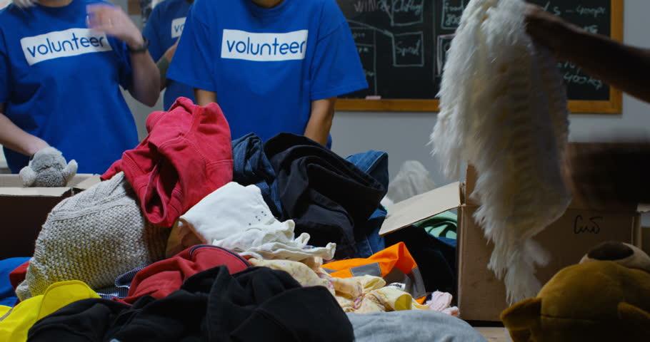Close up shot of a volunteer team packing donation   Shutterstock HD Video #1026548846