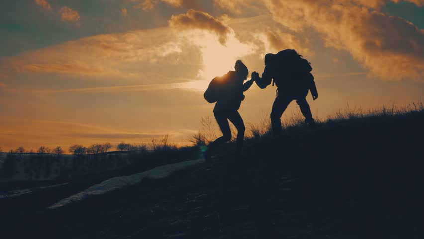 Couple hiking help each other silhouette in mountains. Teamwork couple hiking, help each other, trust assistance, sunset. Man giving hand a woman to help her to climb the mountain. #1026577676