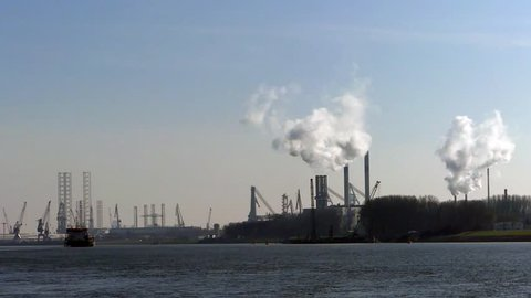 Europoort, Rotterdam, the Netherlands - March 28 2019: Industrial zone, equipment of oil and petro chemical refining, view at distance with chimney stacks pumping steam or smoke