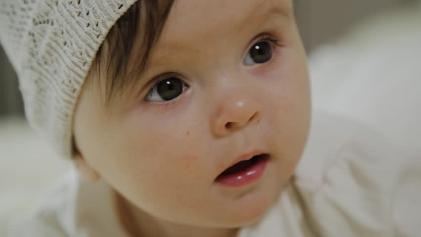 Beautiful little girl is lying on the white bed. | Shutterstock HD Video #1026653216
