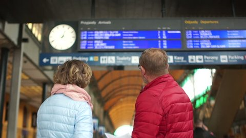 A middle-aged man and woman are waiting for a train on a train platform. Look at the schedule board up