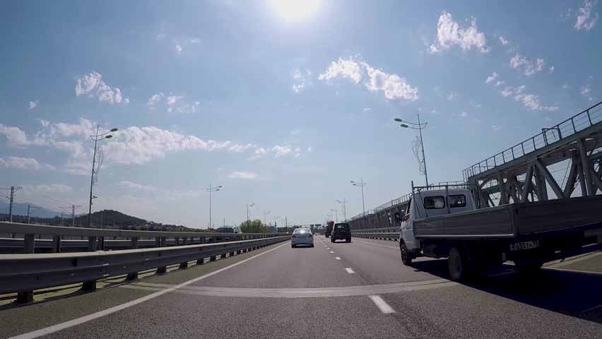 View from car on suburban highway with bridges. Scene. Beautiful landscape with asphalt highway suburb, passing under bridges overlooking blue sky