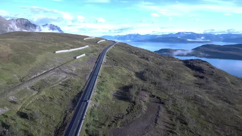 4K drone footage of highway in norway up in the sky birds eye view high ankle view road long road no traffic no people car driving on road