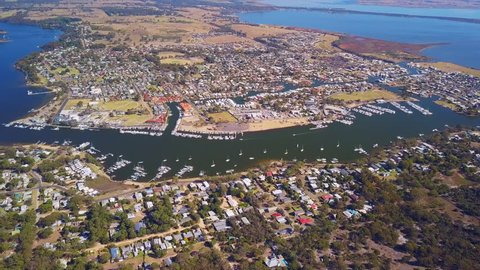 An aerial view of Raymond Island, Australia showing the coastline, water inlets, piers, and moored boats.