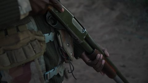 Close up following shot of an anti-poaching camouflaged ranger's gun as he walks into the early morning sunlight