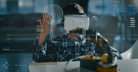 Portrait of boy playing with mechanical arm toy using vr glasses with futuristic augmented reality hologram in living room in slow motion.