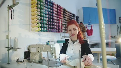 Happy tailor sewing dress with sewing machine in workshop. 4K