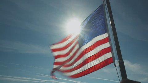 United States flag flapping powerfully in the wind as the sun creates a flare behind it