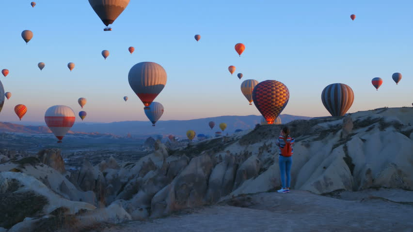 Yoing traveler with backpack looking to the air baloons. sporty girl and a lot of hot air balloons. The feeling of complete freedom, achievement, achievement, happiness #1026792236